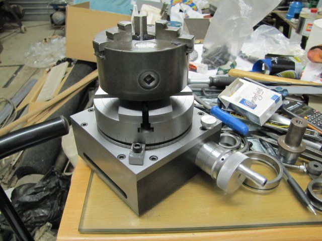 homemade metal lathe chuck. homemade rotary table for a mill. base frame cut from plate and flat bar. material is cast iron. incorporates lathe chuck adaptor. metal