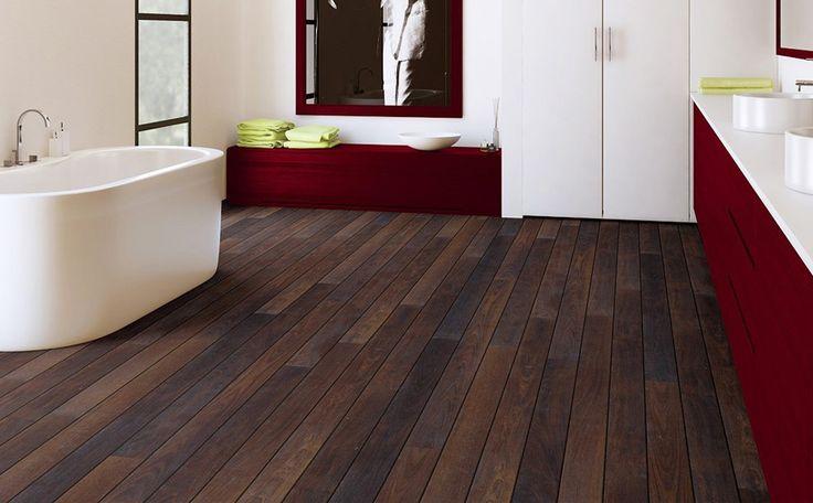 Laminaat van Quick-step in de badkamer: donkere vloer met palissander-look, in combinatie met wit sanitair en gekleurde meubels. Kleurenpalet misschien minder geschikt voor kleine badkamers.