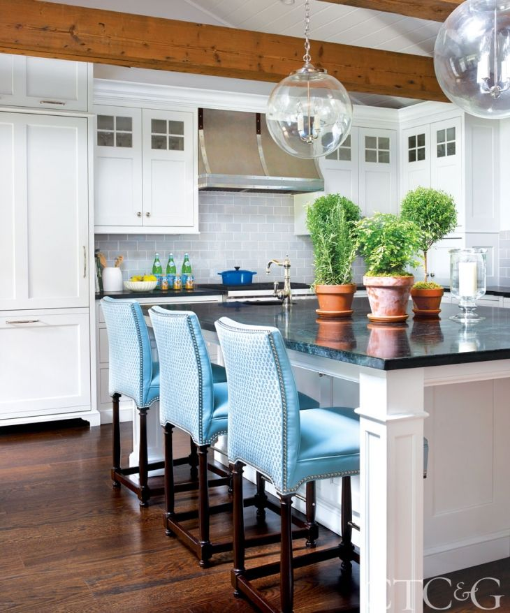In the kitchen, the fronts of the Hickory Chair counter stools are covered in a kid-friendly Kravet leather. The designers added a pop of pattern on the backs with a Sister Parish fabric through John Rosselli & Associates. Pendant lights are from Remains Lighting, reclaimed beams from Reclamation Lumber. Cabinetry is through Saltbox Kitchens.