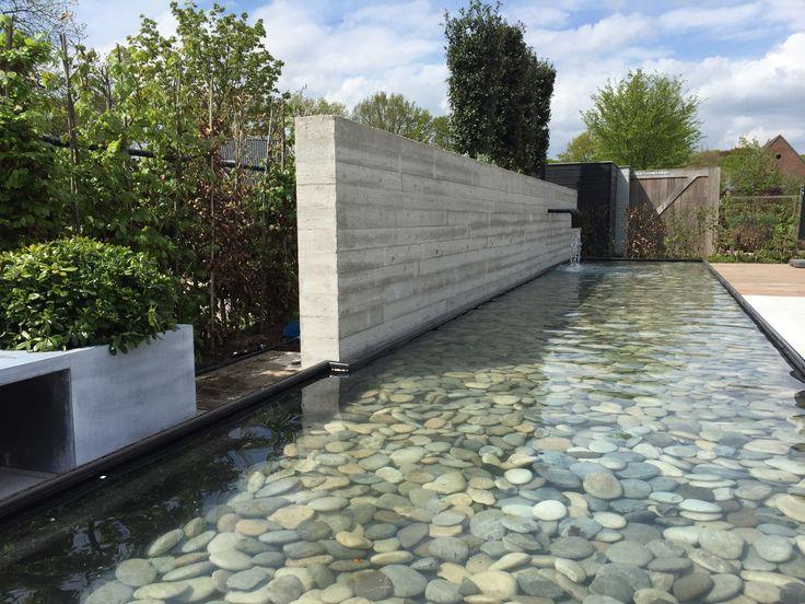 Spiegelvijver met betonnen muur waarin wateruitlopen zijn gemaakt. Groenseizoen.nl
