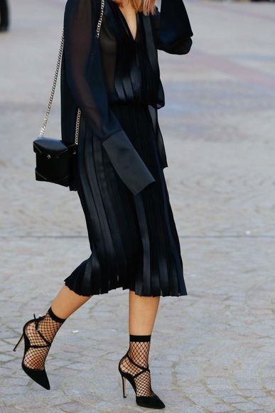 Black pleated dress with fishnet ankle socks and heels - street style from Mercedes-Benz Fashion Week Australia: