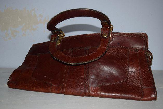 Sie kaufen hier eine wunderschöne vintage Handtasche mit kurzen Riemen in einem schönen rostbraun. Die Tasche besteht aus echtem dickeren stabilem Leder   Der Zustand der Tasche ist noch ok. Die...