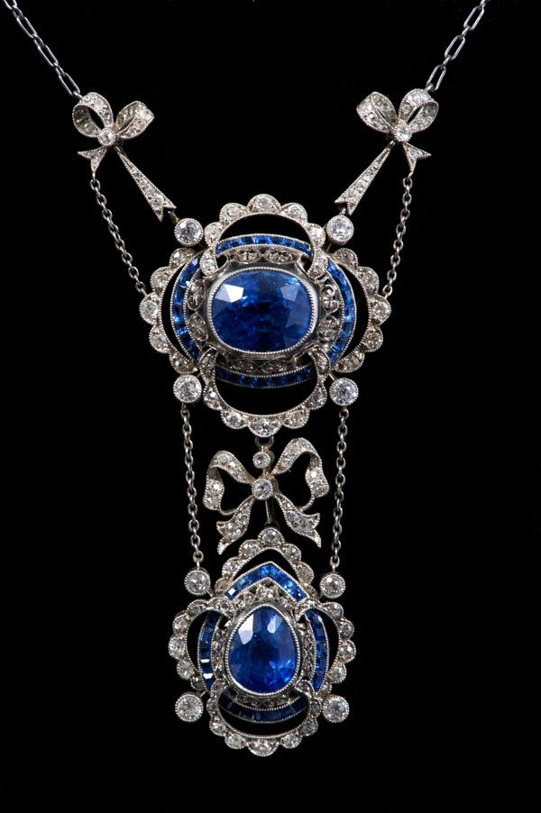 Fine early 20th c. Belle Époque sapphire and diamond necklace, the principle oval mixed cut cornflower blue sapphire estimated to weigh approximately 8.66 carats, in millegrain collet setting and a border of calibre cut blue sapphires, with a further pear cut cornflower blue sapphire, approx. 3.50 carats, all in millegrain setting, suspended from diamond set bows on a trace chain. In original fitted tooled leather case, by Carrington & Co., 130 Regent Street, London.
