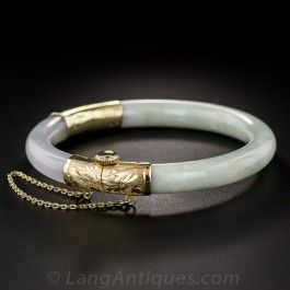 """This Burmese jade, hinged bangle bracelet varies in color form a translucent pastel lavender transcending into pale green to white. The 14k yellow gold hinging mechanism is hand-fabricated and engraved with a secure screw mechanism. There is an ethereal quality to this rather petite bangle bracelet, measuring approximately 7 millimeters in diameter, with an inside circumference slightly shy of 6"""" and an inside diameter of approximately 2"""". Best suited for a small wrist."""