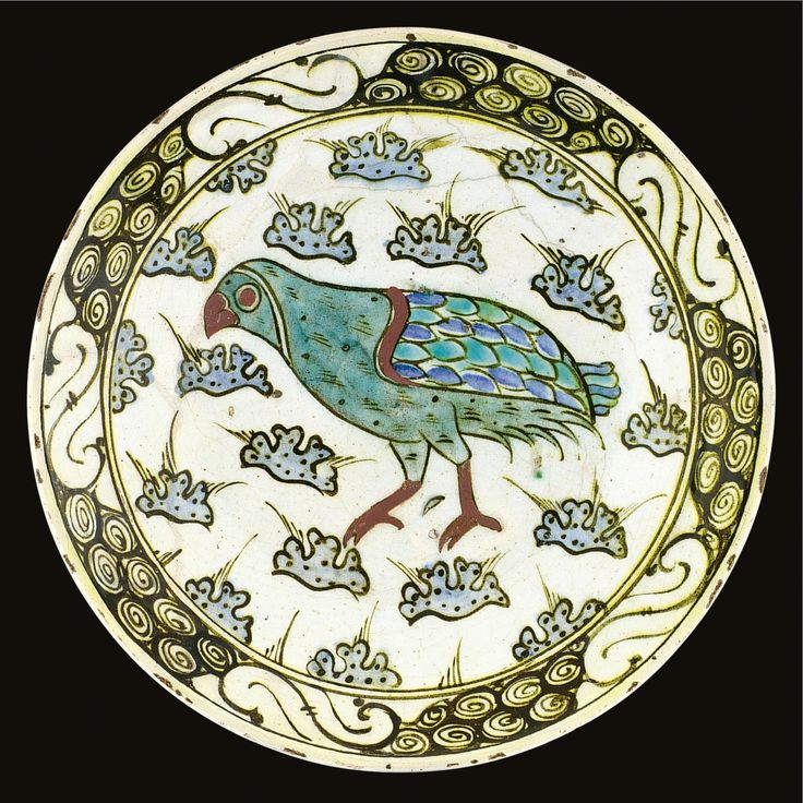 AN IZNIK POLYCHROME POTTERY DISH, TURKEY, FIRST HALF OF 17TH CENTURY the shallow circular form decorated in underglaze red, tones of blue, turquoise and black outlines with a central partridge against a ground of stylised rocks, with a breaking wave border