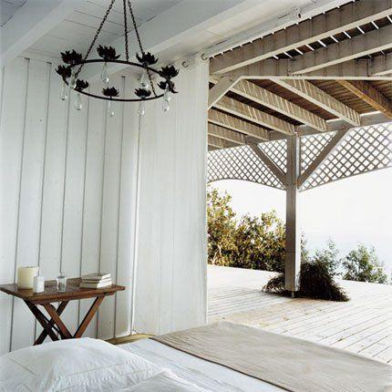 Tout en bardeaux de pin peint en blanc, la chambre est ouverte sur l'extérieur et protégée du soleil par fronton en treillage