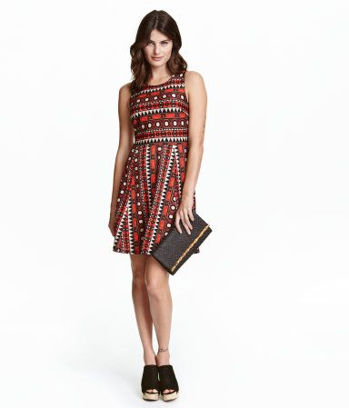 Short, sleeveless dress in thick jersey. Wrapover back section with decorative opening, seam at waist, and gently flared skirt.
