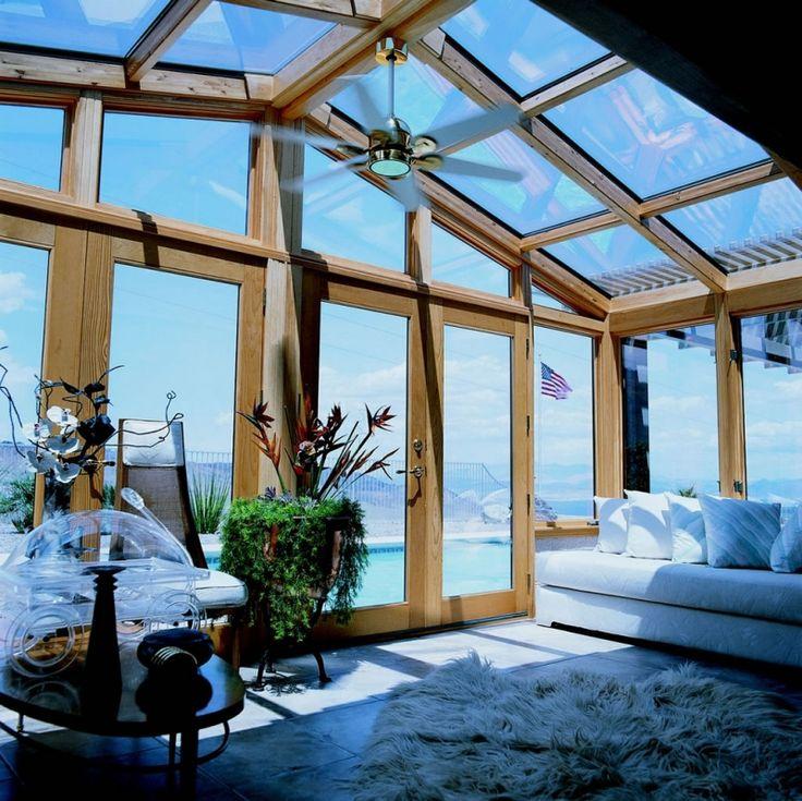 véranda bois avec toiture vitrée et ventilateur de plafond qui donne sur la piscine d'extérieur