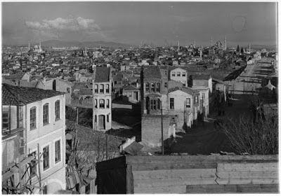 Θέα από το Edirne Kapı (Πύλη Χαρισίου ή Πύλη Πολυάνδρου απ' όπου λέγεται ότι εισήλθε νικητής ο Μωάμεθ ο Πορθητής) προς το Fatih Camii, 1935. Από την κορυφή του Edirne Kapı σε ένα από τα υψηλότερα σημεία των Βυζαντινών Τειχών, ο Artamonoff φωτογραφίζει την πόλη στα πρόθυρα της εποχής του μετασχηματισμού της. Ακολουθώντας τη διαγώνιο του Fevzi Paşa Caddesi το μάτι περνάει τις παλιές γειτονιές μέχρι που φτάνει στον δραματικό ορίζοντα που δημιουργούν μερικά από τα σημαντικότερα οθωμανικά τεμένη…