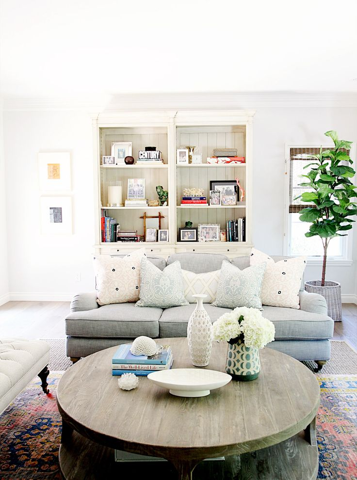 Open space living room with round wooden table, light grey couch, white walls with light artwork, blue and pink patterned pillows, patterned flower vases, white built-in unit, and large plant