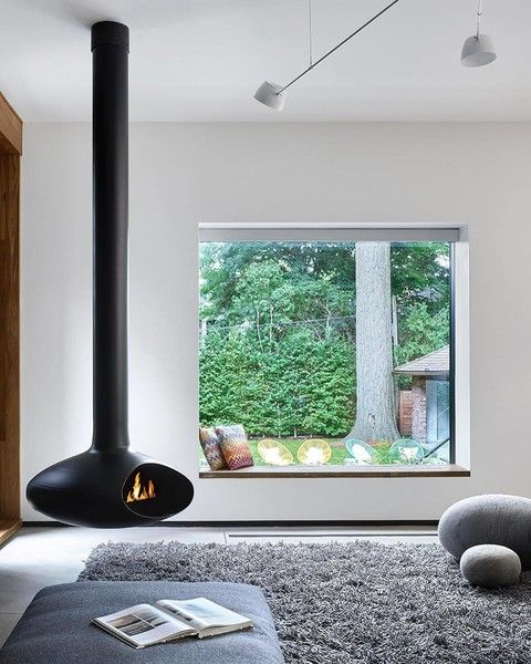 The living space that features a freestanding fireplace looks out through a seated window that perfectly frames the yard.
