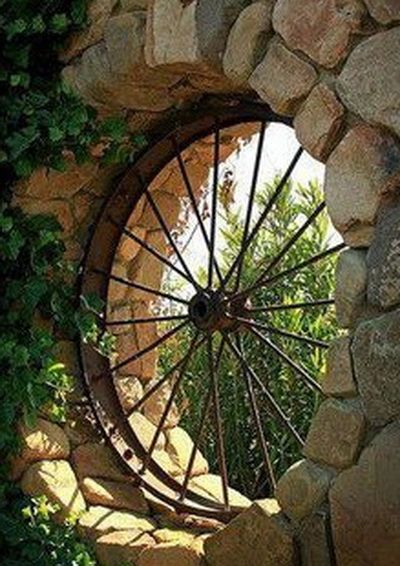 Old metal wagon wheel turned into patio window. Architectural Antiques has a collection of small and large wagon wheels to recreate this look!