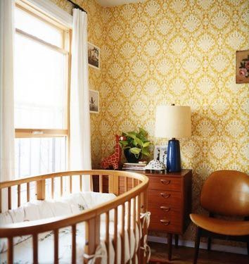 love this sophisticated, timeless nursery with the round crib and the mid-centrury teak furniture and ochre color palette. Why not wallpaper in a baby's room?!