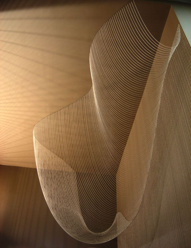 Catenary Veil by Paredes+Alemán arquitectos - Bead-chain curves of different length, all taking their shape through gravity. It is located in front of a set of escalators, so that viewers moving up or down can see the slow overlapping of the curves forming a series of meshes of different densities.