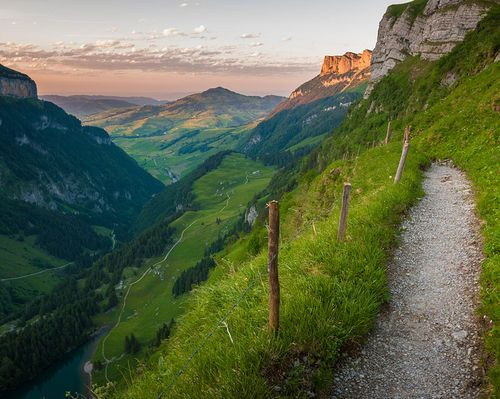 Hiking in the evening on a path high above the Seealpsee, Alpstein,