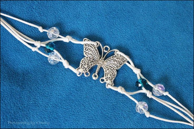 Silver butterfly with blue and white crystal beads on white corded bracelet