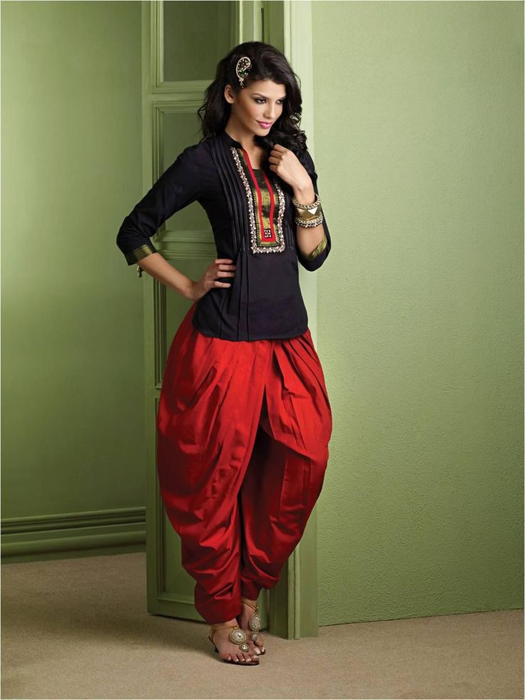 Durga Utsav Collection: deep-red dhoti pants paired with enigmatic black , south cotton kurti, accentuated with Nizam border and heavy embroidery on the placket and styled with oxidized ethnic bangles