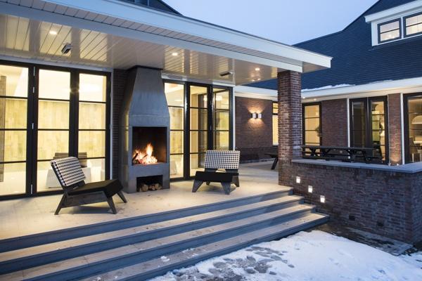 Veranda met stalen buitenhaard in moderne jaren 30 stijl door IIIEIIIO architecten en interieur architecten.