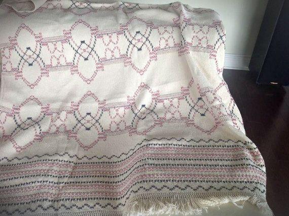 Couverture (jetée) de tissage suédois réalisé à la main avec soin par une artisane québécoise. Parfaite pour tous types de décor. Finition de qualité.  - Mesurant approximativement 2m x 1m (76x42) - Réalisé sur du tissu Monk 100% coton couleur naturel - Fils de laine (différentes teintes de rose et de gris) - Broderie italienne en fil de coton perlé - Bordée de franches sur 2 côtés  La couverture sera emballée avec attention pour offrir en cadeau ou simplement pour vous faire plaisir…