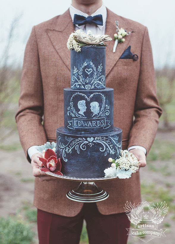 A three-tired vintage inspired wedding is cake created to resemble a chalkboard.