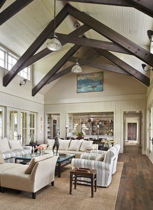 """Exposed scissor trusses rise in the great room. (behind the sofa) was custom-made in France from reclaimed wood, interior designer Rocky Rochon says; the space called for a """"really narrow table."""" (Benjamin Benschneider / The Seattle Times)"""