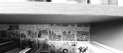 A shelf painted and covered with old comics, masking tape