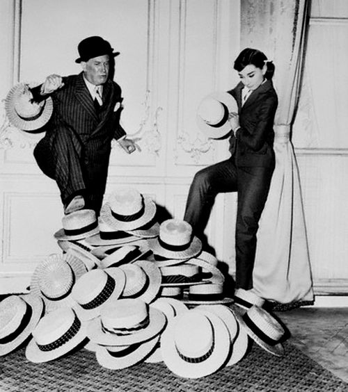 """September 7, 1957: """"A straw hat became... Maurice Chevalier's trademark... but Chevalier is not a fellow to stand still and look back at yesteryear. At the moment he is costarring in a new film Love in the Afternoon in which he plays the role of private detective, complete with the bowler-type hat he is wearing here. Chevalier, with the aid of [costar] Audrey Hepburn... is shown breaking with the past by putting foot and hand into a stock of straw hats."""""""