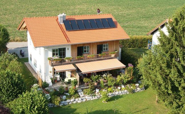 """Das """"Haus Generation"""", welches ohne Keller erbaut wurde, gibt getreu seinem Namen mehreren Generationen ein wohliges Zuhause unter einem Dach.  Die Philosophie der Nachhaltigkeit, die bei der Wohnform bereits verwirklicht wurde, setzte sich in der Wahl der Haustechnik fort. Das wohngesunde Holzhaus wird lediglich über einen gemütlichen Kachelofen mit Warmasserbereiter beheizt. Unterstützung findet der Holzofen durch eine thermische Solaranlage auf dem Hausdach. ..."""