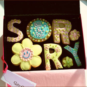 """'Sorry' Cookies Gift Box    8 hand decorated cookies as shown presented in a premium gift box and includes a ribboned gift tag bearing your special message. """"O"""" Cookie can be personalised with up to 3 words. (Add cookie personalisation & gift tag message at checkout).    £20 per gift gift box. Box size 240mm x 170mm"""