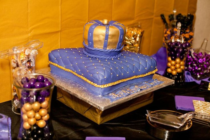 The cake was an amazingly delicious butter cake shaped like a gold crown trimmed in purple on top of a purple pillow. #candytable #desserttable #royalcelebration #crown #purple #gold #black #cake #pillow #pillowcake #crowncake