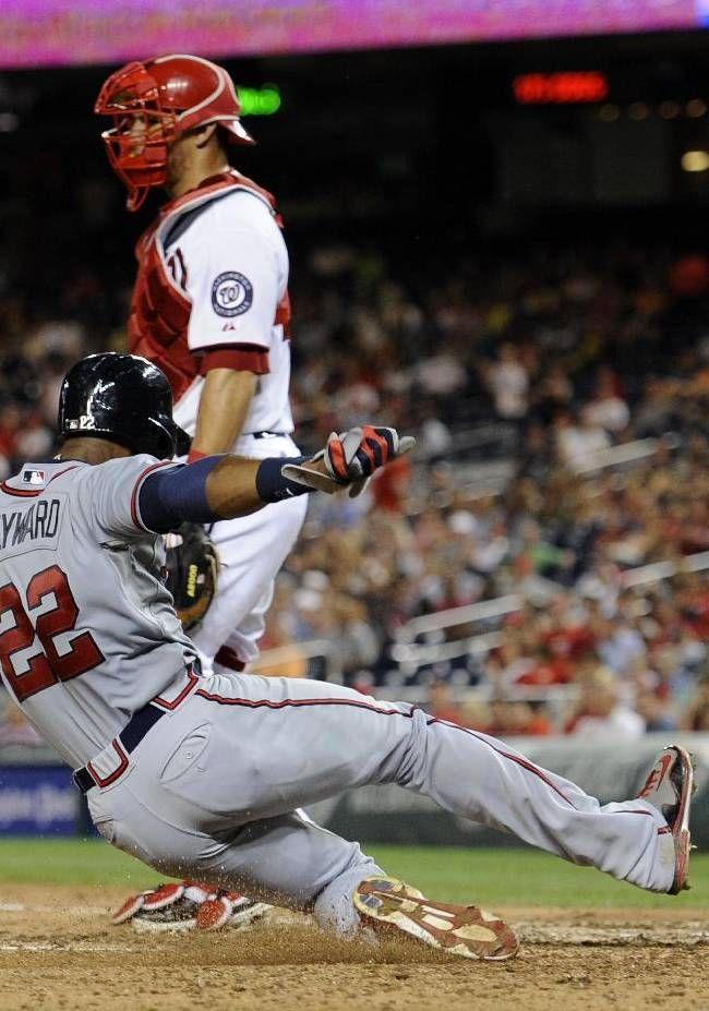 Atlanta Braves' Jason Heyward (22) scores on Justin Upton double during the eight inning as Washington National catcher Wilson Ramos looks on.