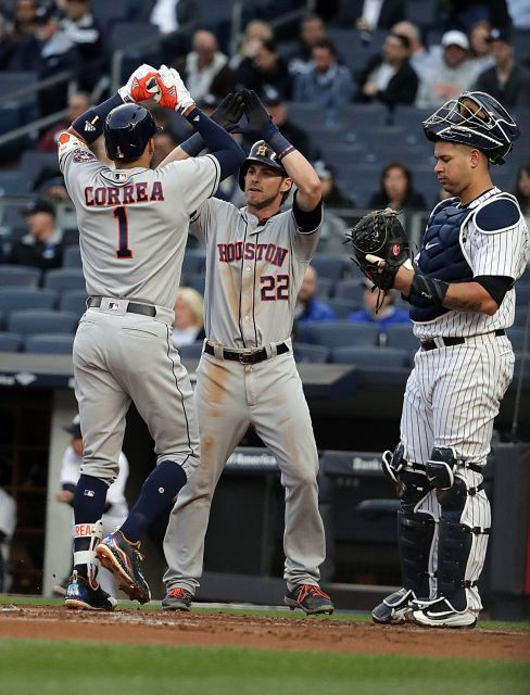 Houston Astros shortstop Carlos Correa high-fives Houston Astros rightfielder Josh Reddick at home after hitting a two-run home run to right during the first inning of the game on Thursday, May 11, 2017 at Yankee Stadium.