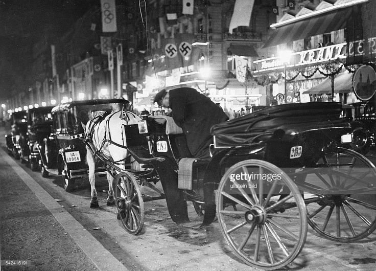 Cab waiting between parked cars in front of the Cafe Kranzler at the street Unter den Linden 25 at nighttime - 1936 - Photographer: Herbert Hoffmann - Vintage property of ullstein bild