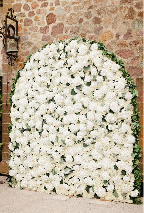 Brides.com: . Dress up a stone wall by creating an elegant, arched flower wall for the ceremony filled with fluffy white hydrangeas. Created by Roni Fleurs.