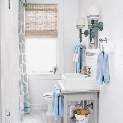 Inject color into a plain white bath with small details like towels that coordinate with banding you can add to sconce shades, window treatments and the shower curtain. Basic 1½-inch blue-satin ribbon, $4 for a 20-yard roll from michaels.com | Photo: Robbie Caponetto | thisoldhouse.com