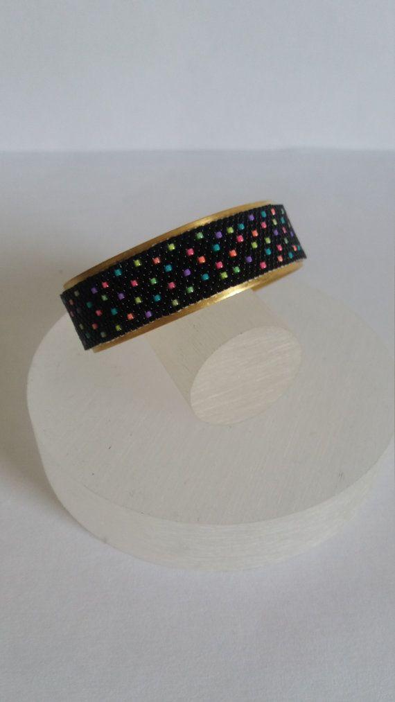 Bracelet Manchette  La structure rigide mais réglable. Elle est en laiton de couleur dorée.  Sur cette structure est fixé un bracelet tissé selon la méthode du peyote. Les perles utilisées sont des des perles Miyuki de couleurs différentes. La couleur dominante est le noir. Sur le fond se dispersent des perles de couleurs fluos mais assorties : rose, orange, bleu, vert, violet, jaune. Les deux perles sont mates et avec des reflets dorés. Elles sont ainsi associées à la structure.  Le tissage…
