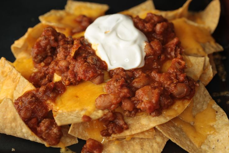 This chili-cheese nacho recipe is topped with a hearty meat and bean chili and plenty of sour cream and sharp cheddar cheese.