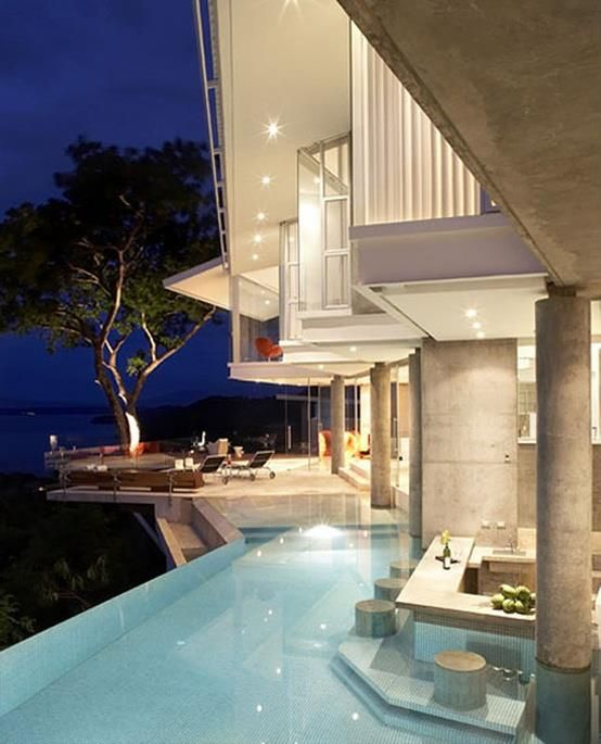 Infinity pool with a swim up bar & tree on the balcony.