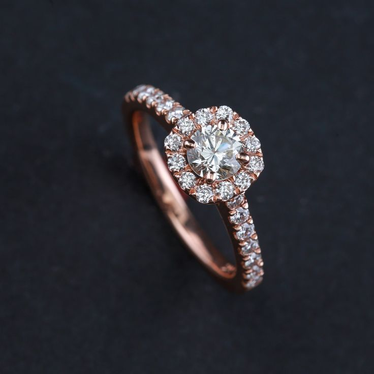 14kt rose gold engagement ring featuring round diamond surrounded by diamond halo and shank - Metal: 14 karat rose gold - Diamond Weight: One .54 carat round center diamond, H color and SI1 clarity an
