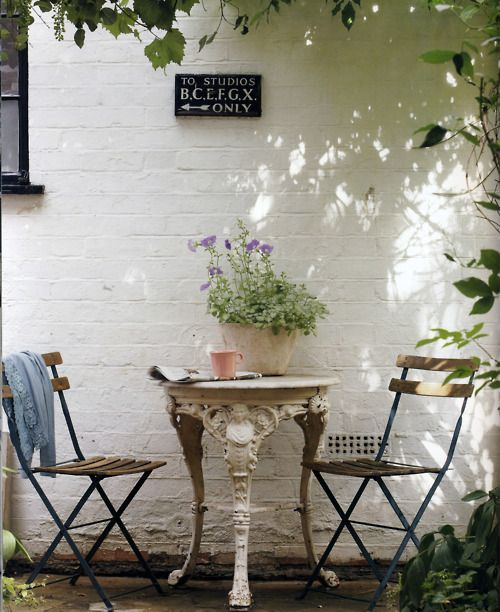 Small terrace or patio with seating for two. Reminds me of France.