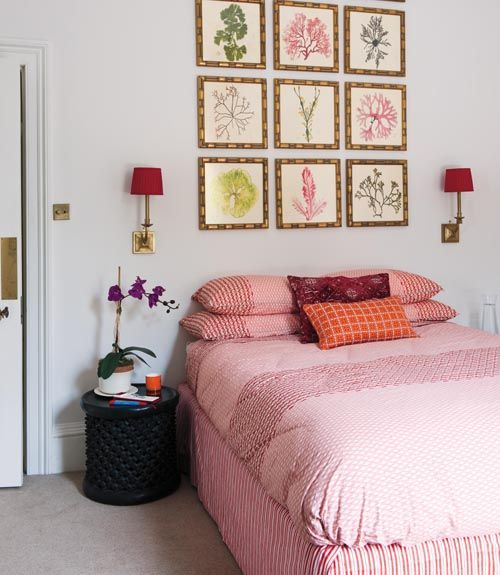 A collection of coral prints overhead serves as a stunning headboard alternative.
