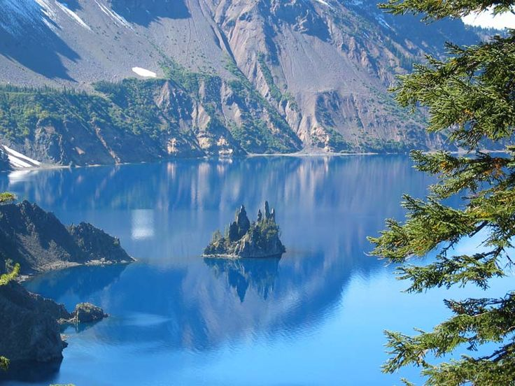 "Crater Lake in Oregon.  A must see if visiting Oregon!  This was a mountain that collapsed forming a caldera. The little rock formation shown here, I believe, is called ""phantom ship."""