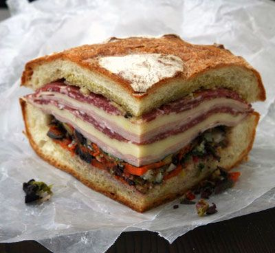 Muffuletta Recipe - Invented by Salvatore Lupo, a Sicilian immigrant, in the 1930s at the Central Grocery in New Orleans, the muffuletta once served—and still does—as a hearty lunch for local workers. The key ingredient is the sandwich's olive relish, which suffuses the bread with its herb-infused flavors. The relish may be prepared up to three days in advance and refrigerated