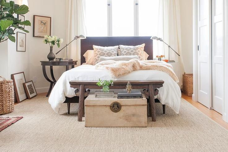 Lovely bedroom features a black tufted bed, placed in front of windows dressed in cream curtains, flanked by mismatched nightstands illuminated by pharmacy table lamps as well as a vintage trunk tucked under a Chinese altar bench placed at the foot of the bed atop a bound sisal rug.