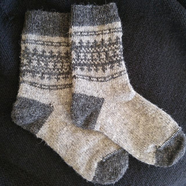 Finial is a sturdy, sport-weight sock pattern, designed for women's size 6-8 feet. It is worked from the top down in a main color and a contrast color, and incorporates Scandinavian stranded colorwork motifs. Heels and toes are worked using short row shaping.