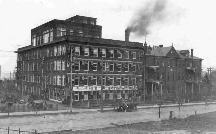 https://flic.kr/p/rTiodf | St. Joseph's Hospital Expansion, 1915 | Date: 1915 Description: Photograph of the exterior of St. Joseph's Hospital in Port Arthur, ON (view from Algoma Street). A white banner on the first storey announces the opening of the hospital's new wing and their Annual Turkey Dinner on November 17th. Dozens of Ontario flags adorn the front of the new expansion. Accession No.: 975.137.1