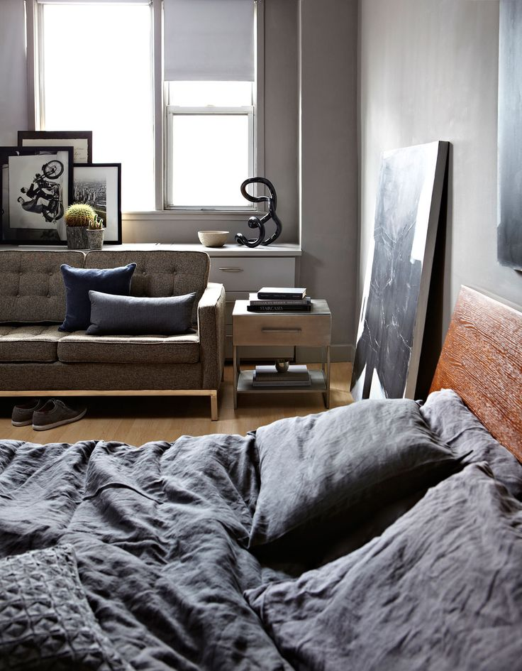 By leaning art against the walls, Ramchandani filled the bedroom with slim yet eye-catching elements, avoiding unnecessary bulk. Behind the streamlined tufted sofa is a framed poster of Charles and Ray Eames, stacked against a photograph of old Manhattan.