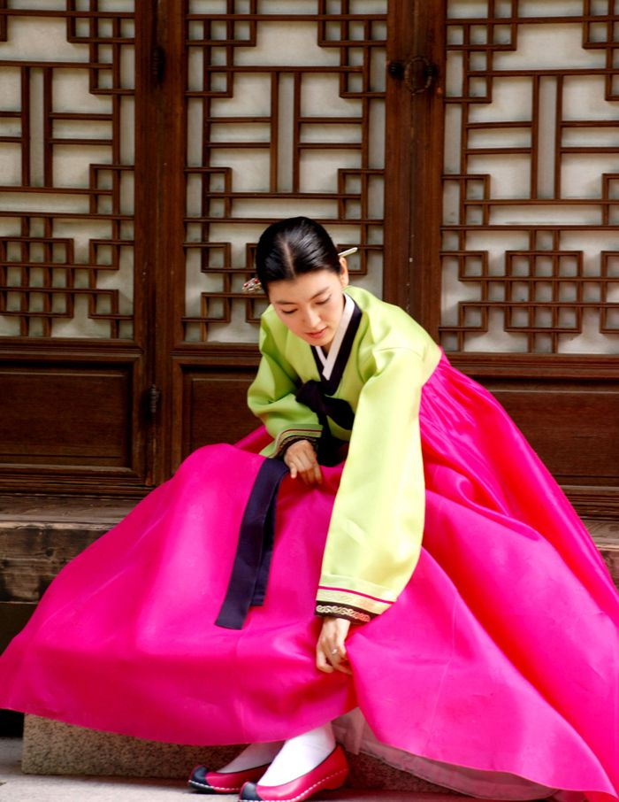 """A woman wearing hanbok puts on """"flower shoes"""" as she leaves the house. http://www.antiquealive.com/Blogs/Hanbok_Traditional_Korean_Clothing.html"""