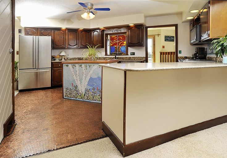 kitchen counter, a colored tile mosaic on the island, and a backsplash