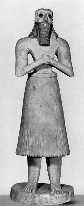 • museum number: IM19752 • excavation number: As. 33:446 • provenience: Tell Asmar  • dimension(s) (in cm): height: 72  • material: stone (veined gypsum); hair and beard colored with bitumen  • date: (ca. 2600 BC)  • description: statue; male, bearded, long hair, bare-chested, wearing flounced skirt; hands folded, holding vessel; eyes inlaid (shell, black limestone), hair and beard painted with bitumen; standing on base with relief decorationon front of base antithetical grou